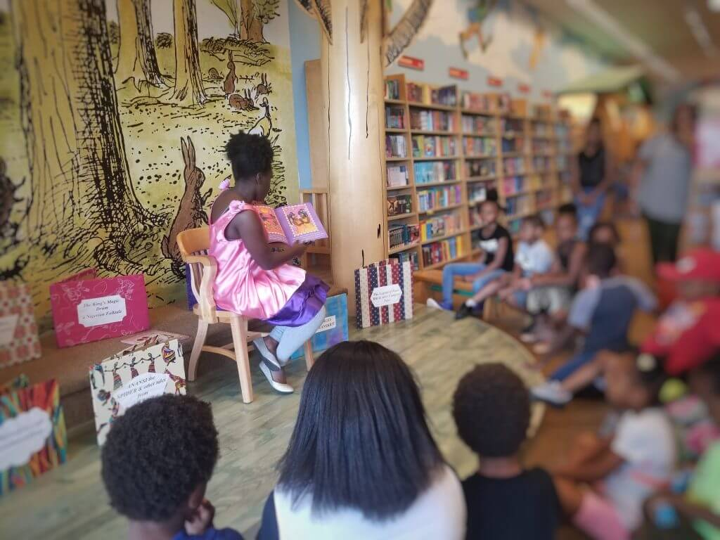 Brown Kids Read teenager reading to kids at a bookstore